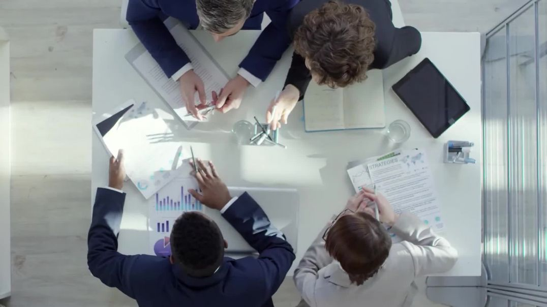 Stock business video of people at table meeting with overhead view of meeting